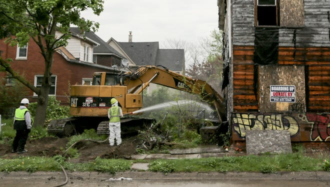 City of Detroit Construction Services workers tear down an abandoned structure across from Bennett Elementary School in Detroit on Thursday May 12, 2016.