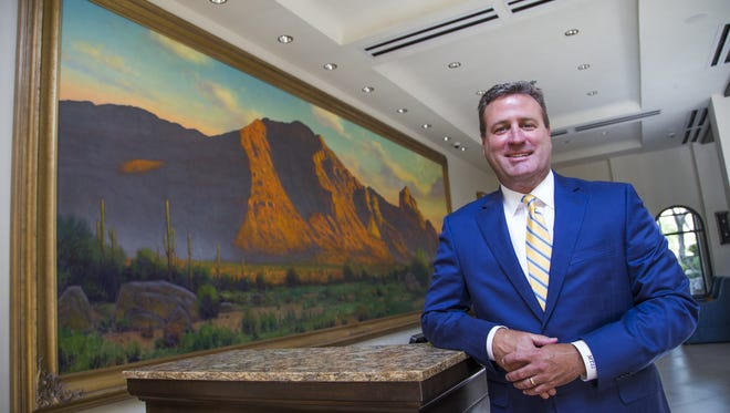 """Mark Snyder owns the Embassy Suites by Hilton Scottsdale Resort.  He shows off a painting of Camelback Mountain by artist Karl Thomas titled """"Guardian of the Valley."""" The painting hangs at the front desk on Wednesday, July 19, 2017."""