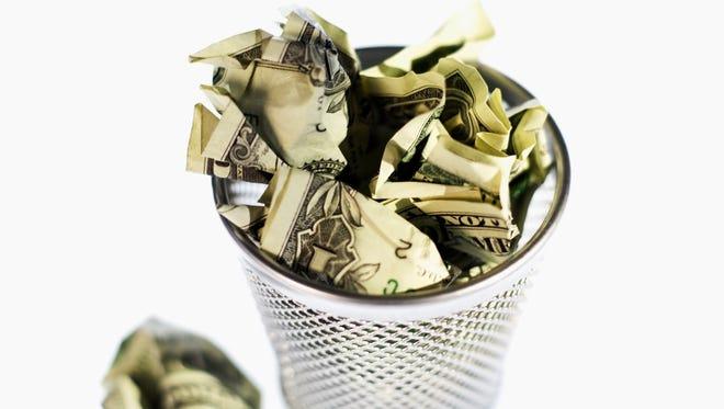 Elevated view of crumpled American dollar bills in rubbish bin