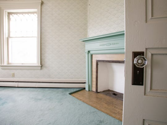 Antique hardware and a fireplace in an upstairs bedroom