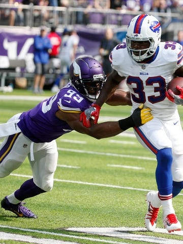 In this Sept. 23, 2018, photo, Buffalo Bills running back Chris Ivory (33) runs from Minnesota Vikings defensive end Danielle Hunter (99) during the first half of an NFL football game, in Minneapolis. Fans are breathing easier in New Jersey and Seattle, and taking in some rarefied air in Western New York. That's what happens when your hapless, helpless and hopeless football teams suddenly turn nasty, effective and victorious. (AP Photo/Bruce Kluckhohn)