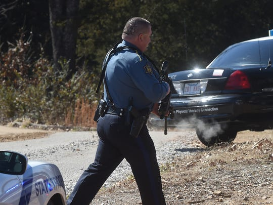 Cpl. Mark Morton of the Arkansas State Police heads to an armed standoff situation Thursday behind Hopper's Dinner Club east of Mountain Home. Officers took Jerry Dean Hopper Jr., 41, into custody after about an hour.