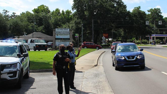 Savannah and Chatham County police officers wave away motorists who arrived at Saturday's school-supply giveaway after inventory ran out.