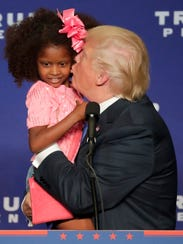 Presidential candidate Donald Trump kisses a girl he