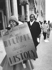In 1986, civil rights activist Rosa Parks carries a sign as part of a picket line in front of General Motors Headquarters. Behind her is Rep.John Conyers Jr., D-Detroit.