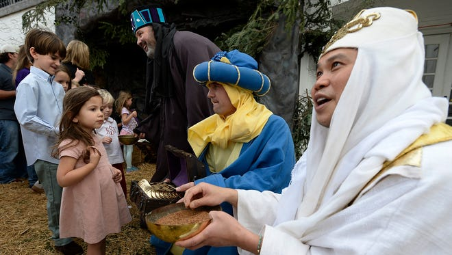Dressed as the three wise men, Justin Gung, right, Phillip Harrison, center, and Tate Rich talk with a group of children during the Walk Thru Bethlehem reenactment at the Woodmont Christian Church on Sunday, Dec. 13, 2015, in Nashville.