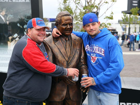 Jody Pitre (L) and Mike Daniels, both of Syracuse share their beers with the statue of former Bills owner Ralph Wilson Jr. outside the stadium.