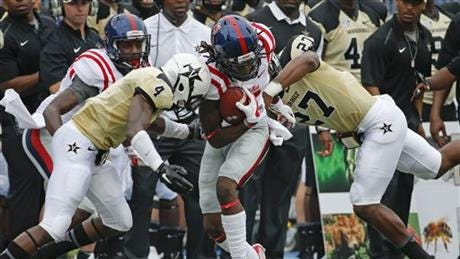 Quincy Adeboyejo tries to run through a pair of Vanderbilt defenders.