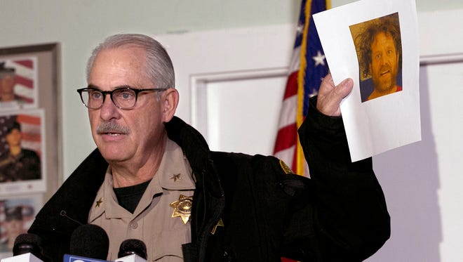 Phil Johnston, the assistant sheriff for Tehama County, displays a booking photo, from a prior arrest, of Kevin Janson Neal, during a news conference, Wednesday, Nov. 15, 2017, in Rancho Tehama Reserve, Calif.