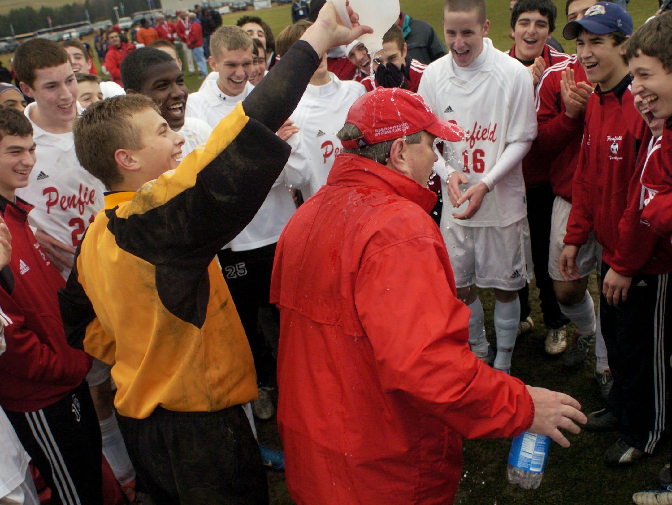 Former Penfield's goal keeper Kyle Zinter dumps a gallon of water on head coach John Butterworth after beating Massapequa in the 2004 State Class AA Boys Soccer Championship.