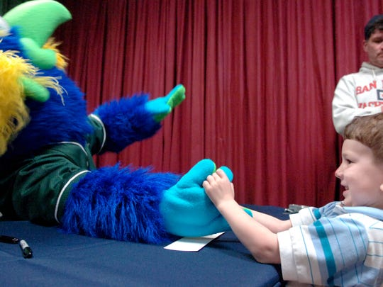 Chad Fauth, 4, of York, arm wrestles DownTown Yorkie, the new mascot for the York Revolution, at the unveiling ceremony for the mascot at DreamWrights Youth and Family Theatre in 2007.