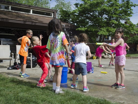 Alyssa Korte, far right, squirts a group of runners after the Kids Fun Run for Paws on Saturday, June 4, 2016, on Grosse Ile. The event, organized by 8-year-old Sarah Shamus, was a fund-raiser for the Grosse Ile Animal Shelter.