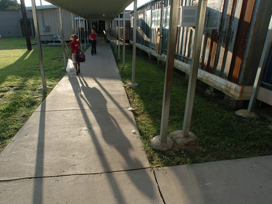 Students walk to classrooms at Evangeline Elementary. The school has 28 temporary buildings.