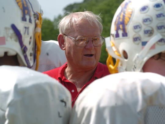 Butch Stoker is seen talking to players in this file photo when he was the head football coach at Alexandria Senior High School.