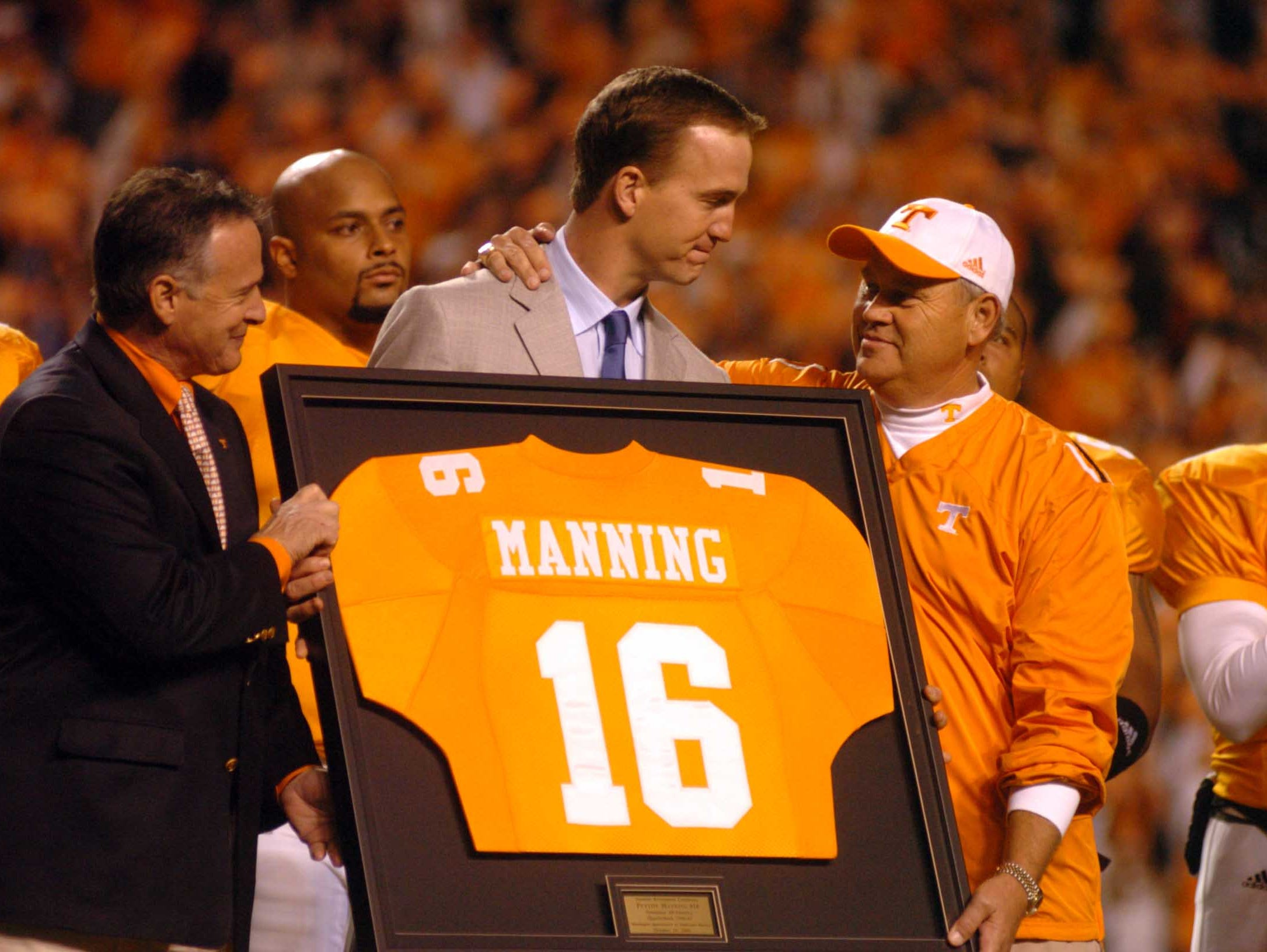 Former Tennessee quarterback Peyton Manning, center, is congratulated by coach Phillip Fulmer as his jersey is retired Saturday, Oct. 29, 2005, at Neyland Stadium. UT President John Petersen is at left.