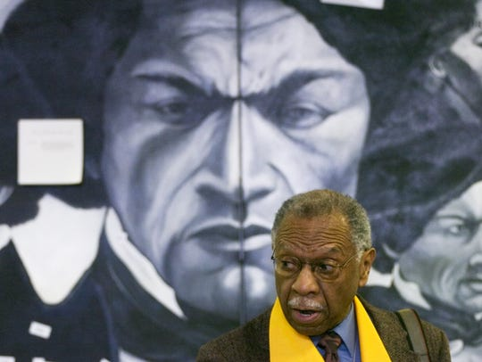David Anderson in front of a mural with Frederick Douglass
