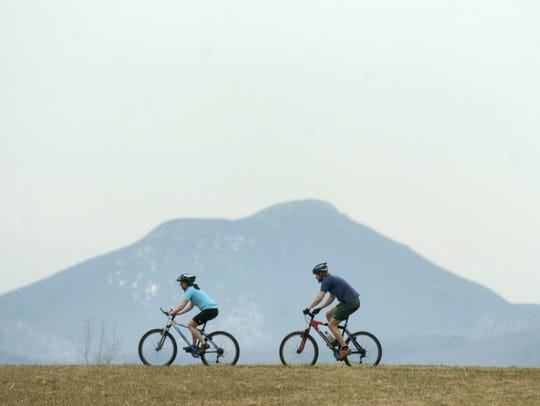 Mountain bikers are flanked by Camels Hump mountain