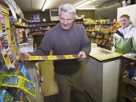 Bob Cavanaugh, owner of Cavanaugh's Grocery and Delicatessen on Leroy Street in Binghamton, left, sells a New York Lottery instant scratch-off game Monday to customer Sarah Lewis, 25, of Binghamton. Lewis said she is a regular customer of the lottery games.