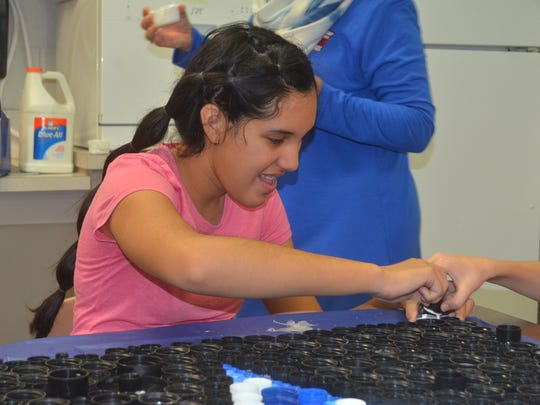 Jimena Moore-Pimentel dips a black bottle cap in glue for an art project with Borderless Arts Tennessee at Station Camp Middle School.