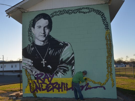 Mural artist Bryan Deese spray painted a chain bordering