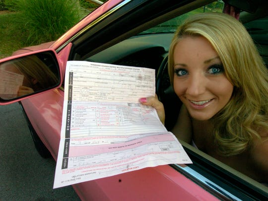 Justis Richert poses in her car with her speeding ticket for 92 mph in a 70 mph zone she got from Tennessee Trooper Randy Moss before performing oral sex on him in May 2007.