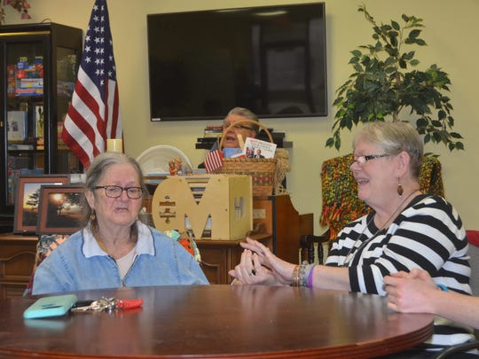 Linda X and Jean McCaslend hold hands while singing hymns at The Veranda in Gallatin.