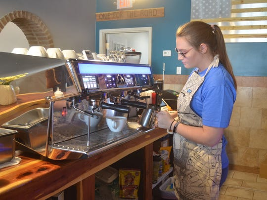 Barista Rheanna Waggoner steams milk for a customer's latte at Milo Coffee House in Portland, Tennessee.
