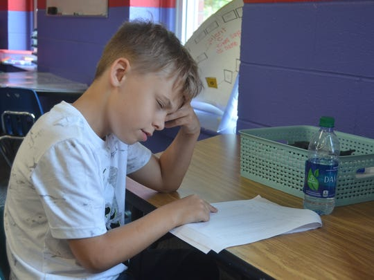 Seven-year-old Gregory McMillan thinks as he practices reading a list of sight words at the Hendersonville's SMORE Reading Camp July 2, 2018.