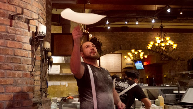 Kyle Myers makes a pizza at Capone's in downtown Fort Myers.