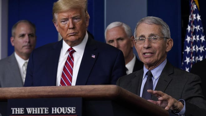 President Donald Trump listens as Dr. Anthony Fauci, director of the National Institute of Allergy and Infectious Diseases, speaks during a coronavirus task force briefing March 20 at the White House.