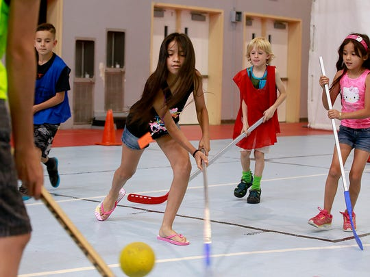 Lucyalize Hernandez, 11, plays floor hockey on Friday at the Aztec Boys and Girls Club. The organization has seen enrollment in its summer program increase by 20 percent at the same time that it is receiving less funding from agencies like San Juan United Way.