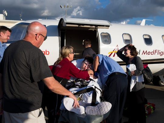 Medical crews help transport Mitchell Reidy, 19, to