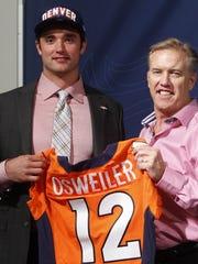 Denver Broncos vice president John Elway, right,  poses