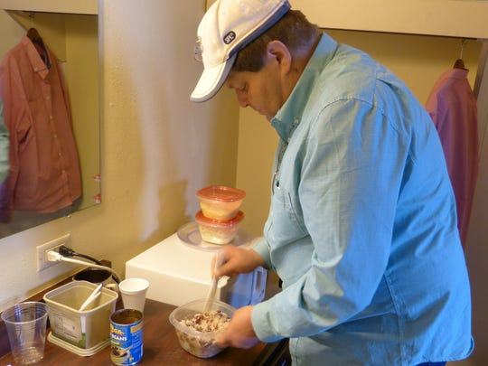Vernon Price prepares dinner inside his room at the Ponderosa Inn. Through the Bridges to Housing program, Price was able to move into the motel last October.