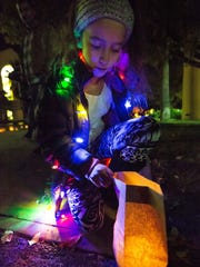Mia Velez looks to see what is inside of a luminaria