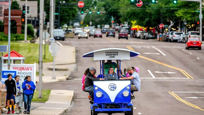 Dianna White, at the steering wheel, and her husband Jody Summers, standing behind her, host a 60th birthday party for Mary Ardis and her family aboard the Pedal Your Own Party bus down Prospect Avenue in Peoria Heights.