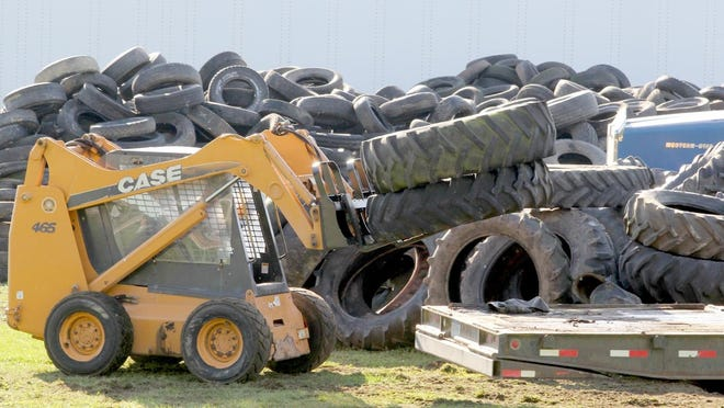 Workers load collected tires onto a flat-bed trailer during a previous tire collection event.