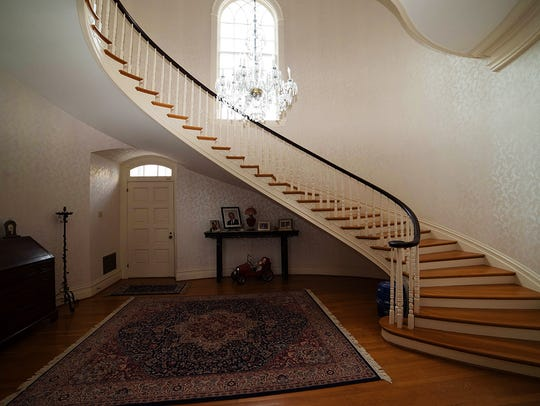 The grand staircase graces the entrance of the home.