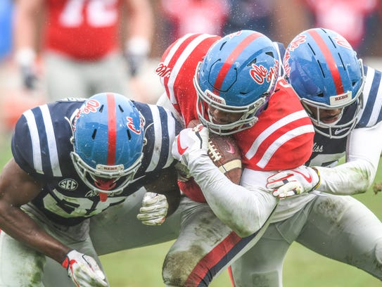 Ole Miss' Octavious Cooley (15), center, is tackled