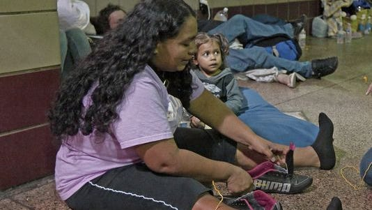 Doris Suyapa of Honduras was among hundreds of mostly Central American women and children caught crossing from Mexico into South Texas and flown to Arizona. Officials dropped many of them off at Phoenix and Tucson Greyhound stations, overwhelming the stations and humanitarian groups trying to help.