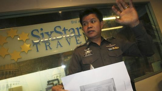 A Thai policeman shows a copy of Italian Luigi Maraldi's stolen passport as he visits the Six Stars Travel for questioning in Pattaya, Chonburi province, Thailand, March 10, 2014.
