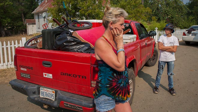 Ronnette Murray, left and her son Brody Crippen, 13, stand next to their pick-up truck which is holding all they could carry as they evacuated from their Lewiston home late Sunday evening and drove to stay with friends in Weaverville. The family is due to leave for Florida for a Little League Baseball tournament her sons are competing in and they do not now if they will have a home to return to. The Carr Fire advanced towards Trinity County late Sunday forcing new evacuations. The fire is only at 20 percent containment as of Monday morning.(KELLY JORDAN / USA TODAY NETWORK)
