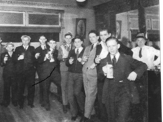 Men hold their drinks at Murphy's Bar on Burlington