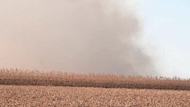 Smoke rises from a grass/field fire behind a field of corn south of Ewart in Poweshiek County. The fire burned approximately 500 acres before being extinguished by fire fighters from three counties.