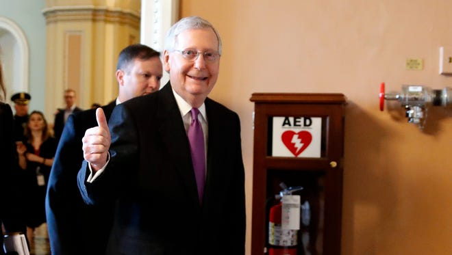 Senate Majority Leader Mitch McConnell of Ky., makes the thumbs up sign as he leaves the Senate floor after reaching an agreement to advance a bill ending the government shutdown, Jan. 22, 2018.