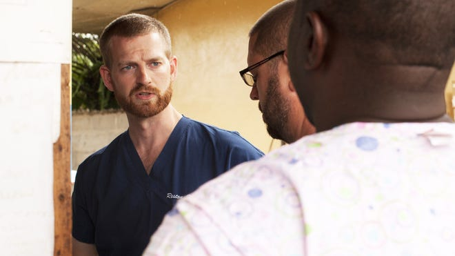 Dr. Kent Brantly, left, one of the two Americans who contracted Ebola, works at an Ebola isolation ward at a mission hospital outside of Monrovia, Liberia.