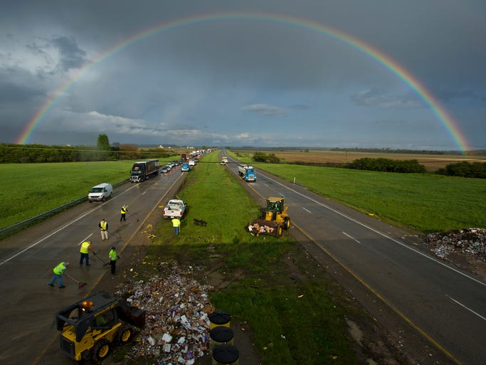 A rainbow forms over Interstate 74 as work crews clean up debris after a semitrailer ran into the Indiana 341 bridge support Friday, May 16, 2104, near Hillsboro. One fatality was reported at the scene.