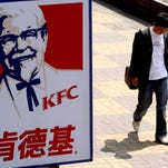 In this Thursday, March 29, 2007, file photo, a man walks past a sign for KFC in Shanghai, China.