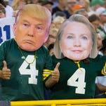 Green Bay Packers fans wear masks of Donald Trump and Hillary Clinton.
