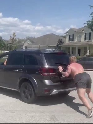 UCF offensive lineman Parker Boudreaux pushes an SUV as part of his home workout during the coronavirus pandemic.